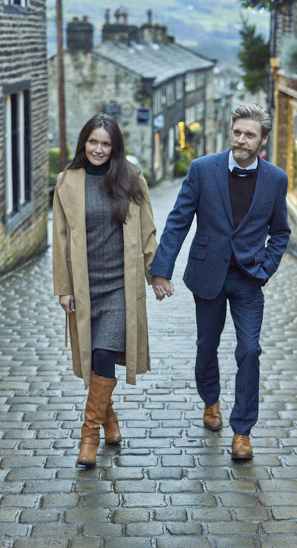 A couple walking along a cobbled street in the historic village of Haworth in West Yorkshire, stone cottages in the background.